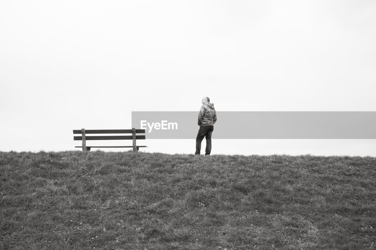 one person, rear view, field, full length, land, real people, nature, lifestyles, sky, copy space, standing, leisure activity, men, landscape, day, tranquility, plant, casual clothing, beauty in nature, outdoors