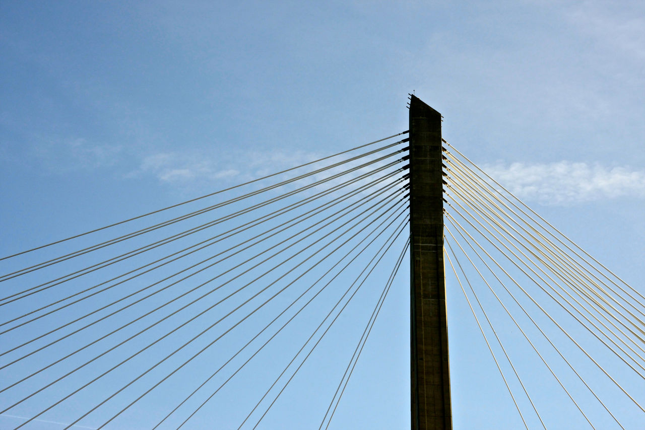 sky, low angle view, cloud - sky, cable, architecture, bridge, connection, bridge - man made structure, built structure, cable-stayed bridge, engineering, suspension bridge, nature, transportation, day, blue, steel cable, tall - high, outdoors, power supply