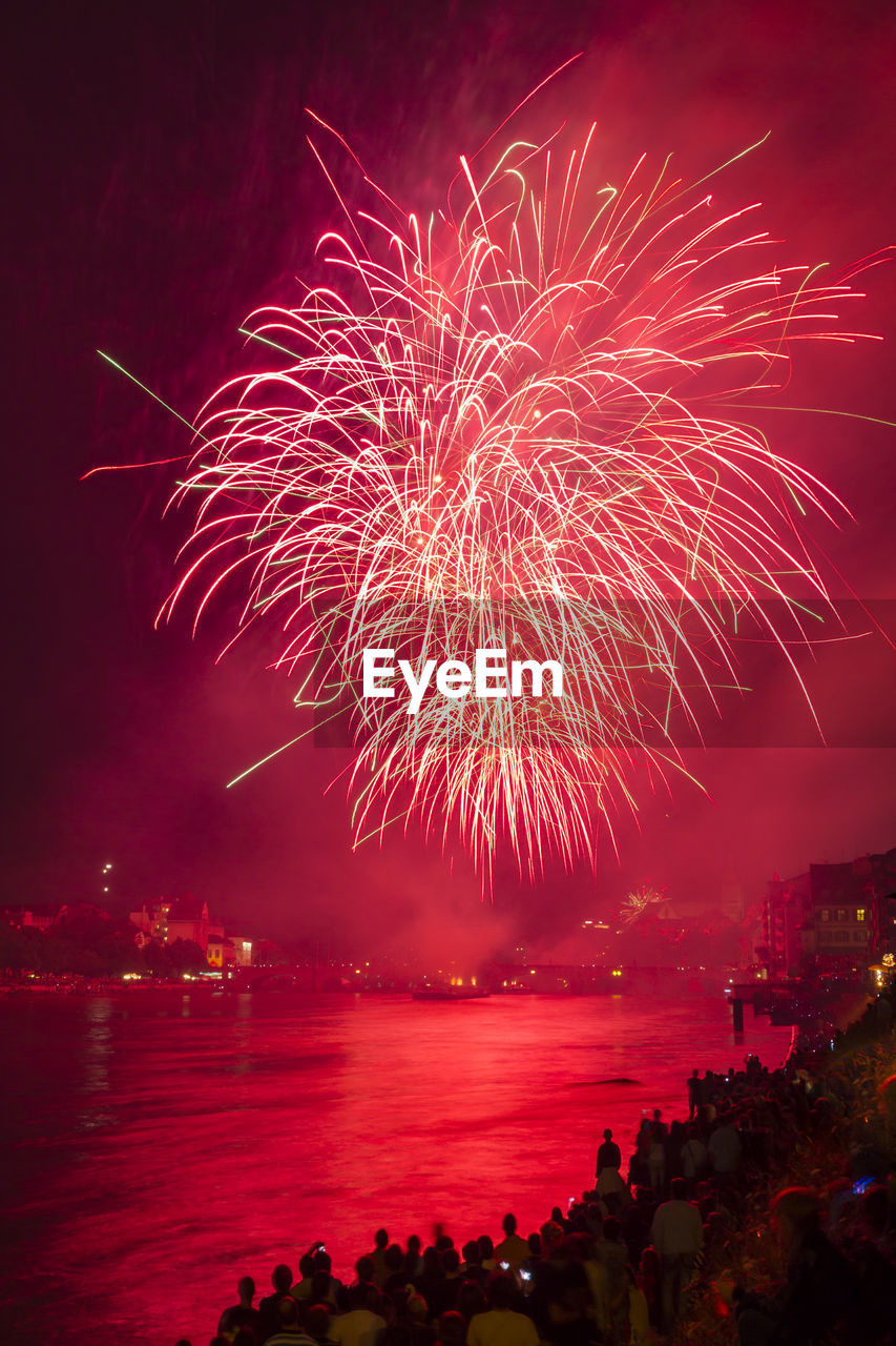 firework display, celebration, night, firework - man made object, illuminated, exploding, long exposure, sky, blurred motion, event, arts culture and entertainment, sea, outdoors, motion, low angle view, water, scenics, no people, multi colored, beauty in nature