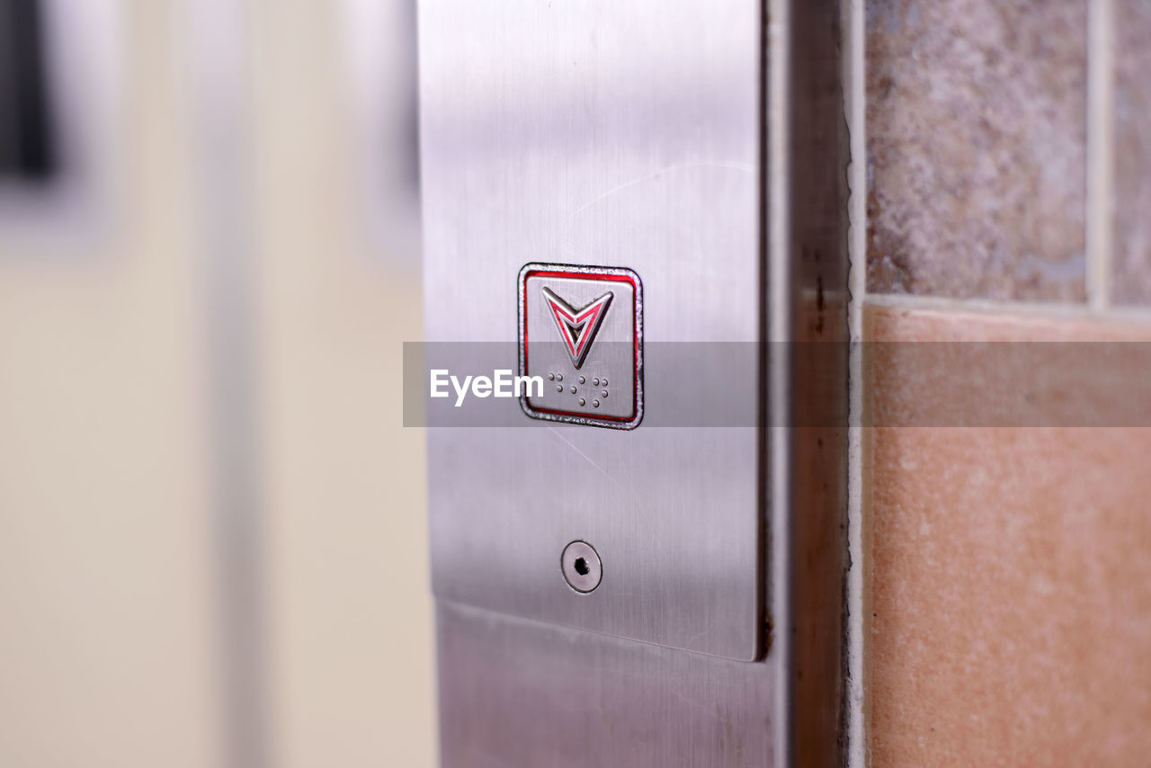 Close-Up Of Down Arrow Elevator Button On Wall