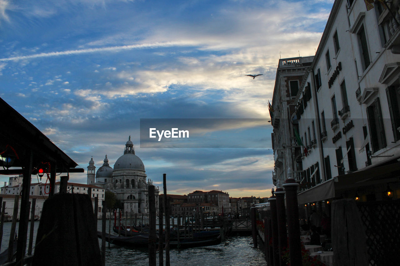 building exterior, architecture, built structure, sky, water, cloud - sky, dome, place of worship, nautical vessel, mode of transport, transportation, outdoors, spirituality, religion, city, travel destinations, day, waterfront, moored, no people, sunset, nature, gondola - traditional boat
