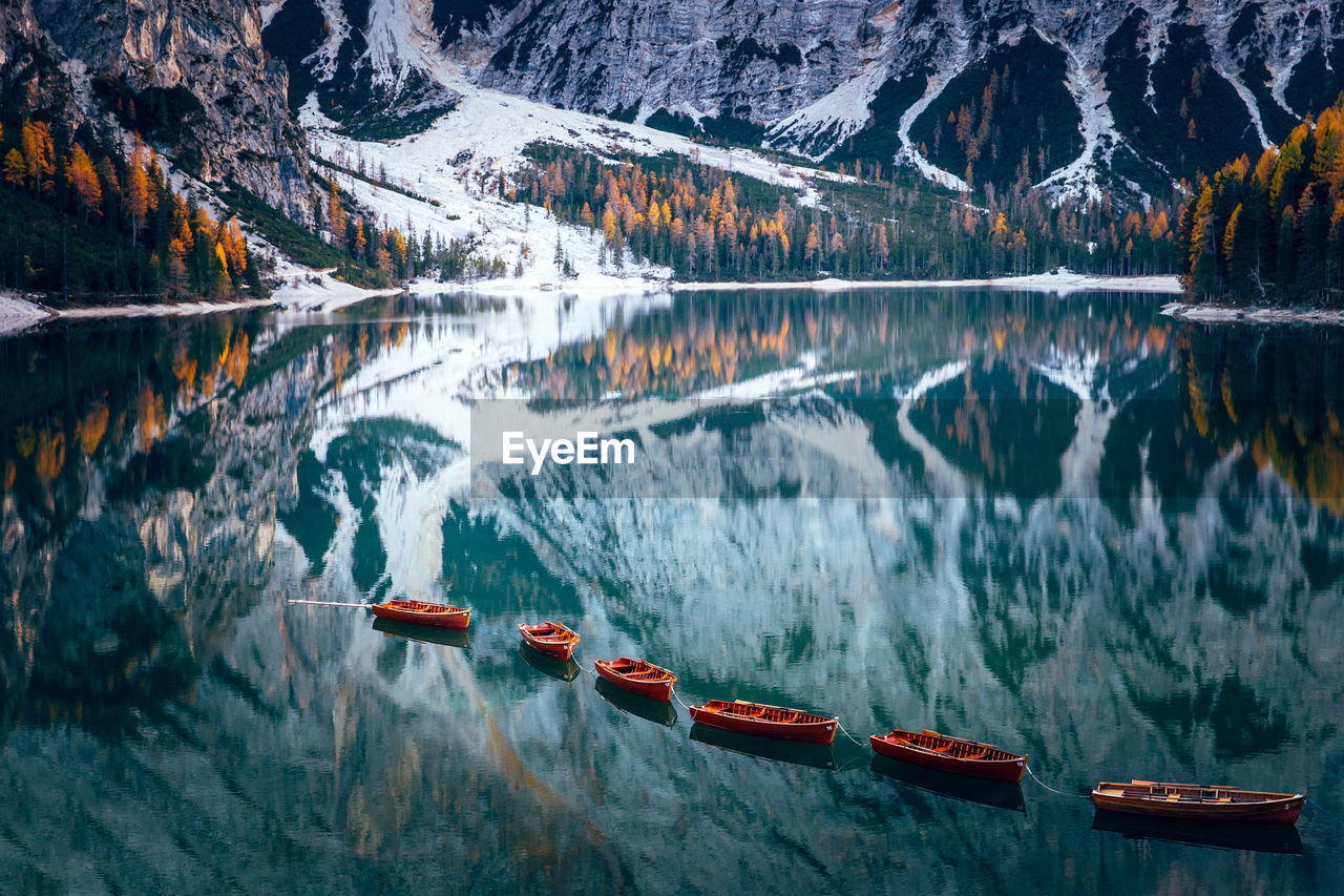 water, scenics - nature, mountain, nautical vessel, lake, beauty in nature, reflection, nature, transportation, no people, mode of transportation, motion, tranquil scene, tranquility, mountain range, non-urban scene, day, red, outdoors, formation