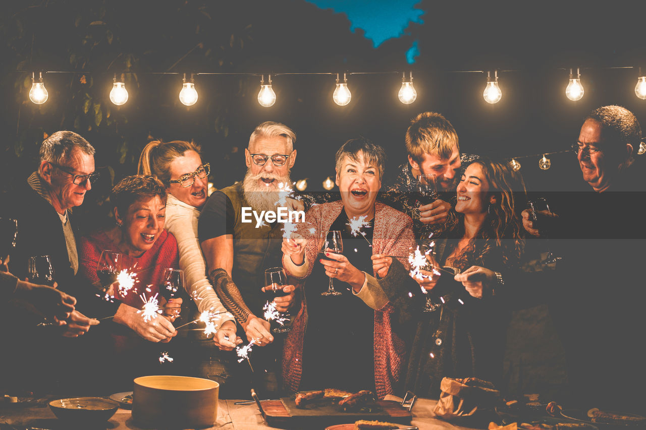 illuminated, group of people, togetherness, real people, men, night, adult, group, males, women, food and drink, friendship, lifestyles, drink, refreshment, smiling, leisure activity, happiness, emotion, glowing, nightlife, glass