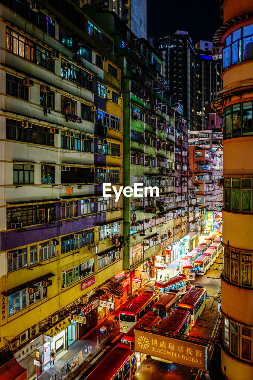 city, architecture, built structure, building exterior, illuminated, building, night, city life, choice, no people, outdoors, variation, residential district, abundance, large group of objects, window, transportation, multi colored, mode of transportation, skyscraper