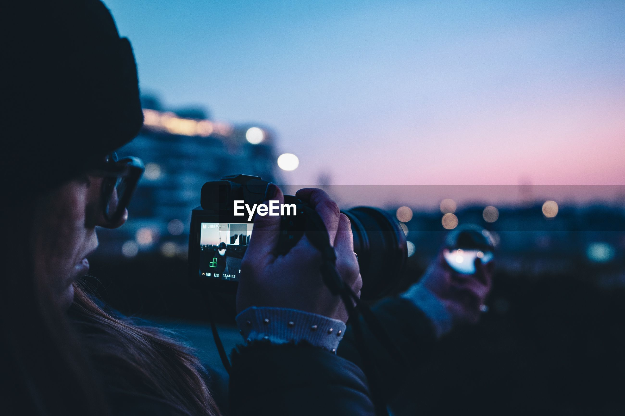 technology, wireless technology, photography themes, activity, real people, photographing, smart phone, portable information device, mobile phone, holding, leisure activity, sky, communication, lifestyles, people, illuminated, screen, night, connection, digital camera, outdoors, nightlife