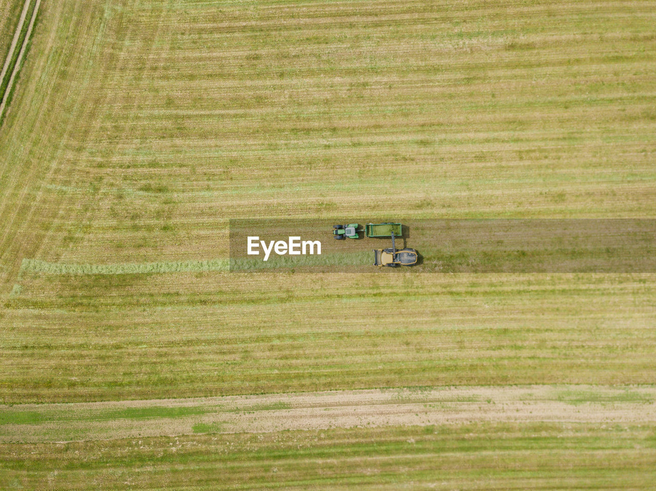 field, land, landscape, environment, land vehicle, green color, day, mode of transportation, transportation, plant, rural scene, nature, no people, farm, agricultural machinery, agriculture, agricultural equipment, tractor, grass, growth, outdoors