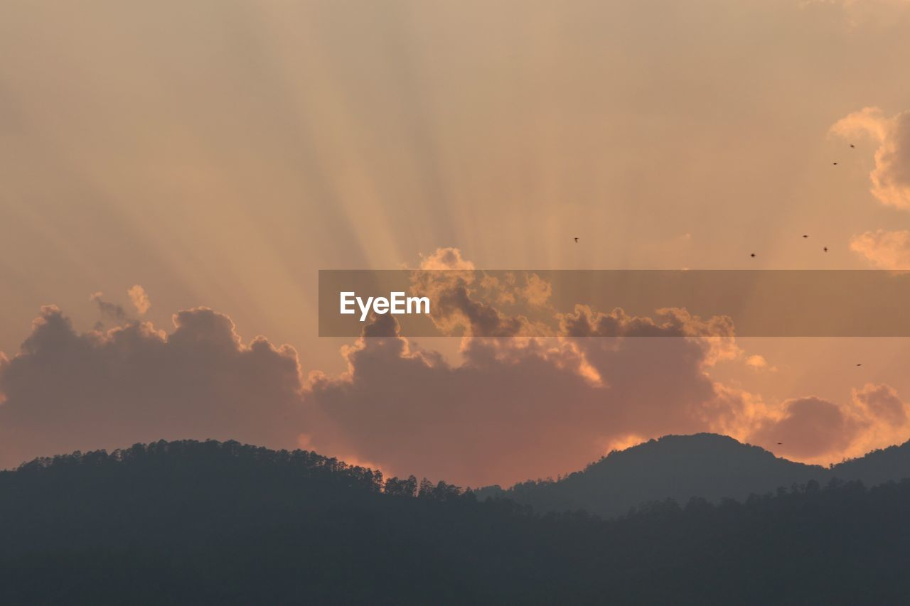 View Of Silhouetted Mountains Against Cloudy Sky At Dawn
