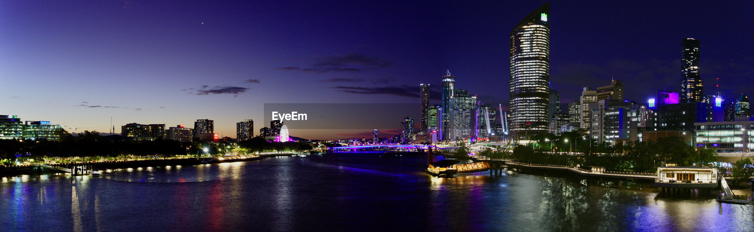 PANORAMIC VIEW OF ILLUMINATED CITY BUILDINGS AT NIGHT