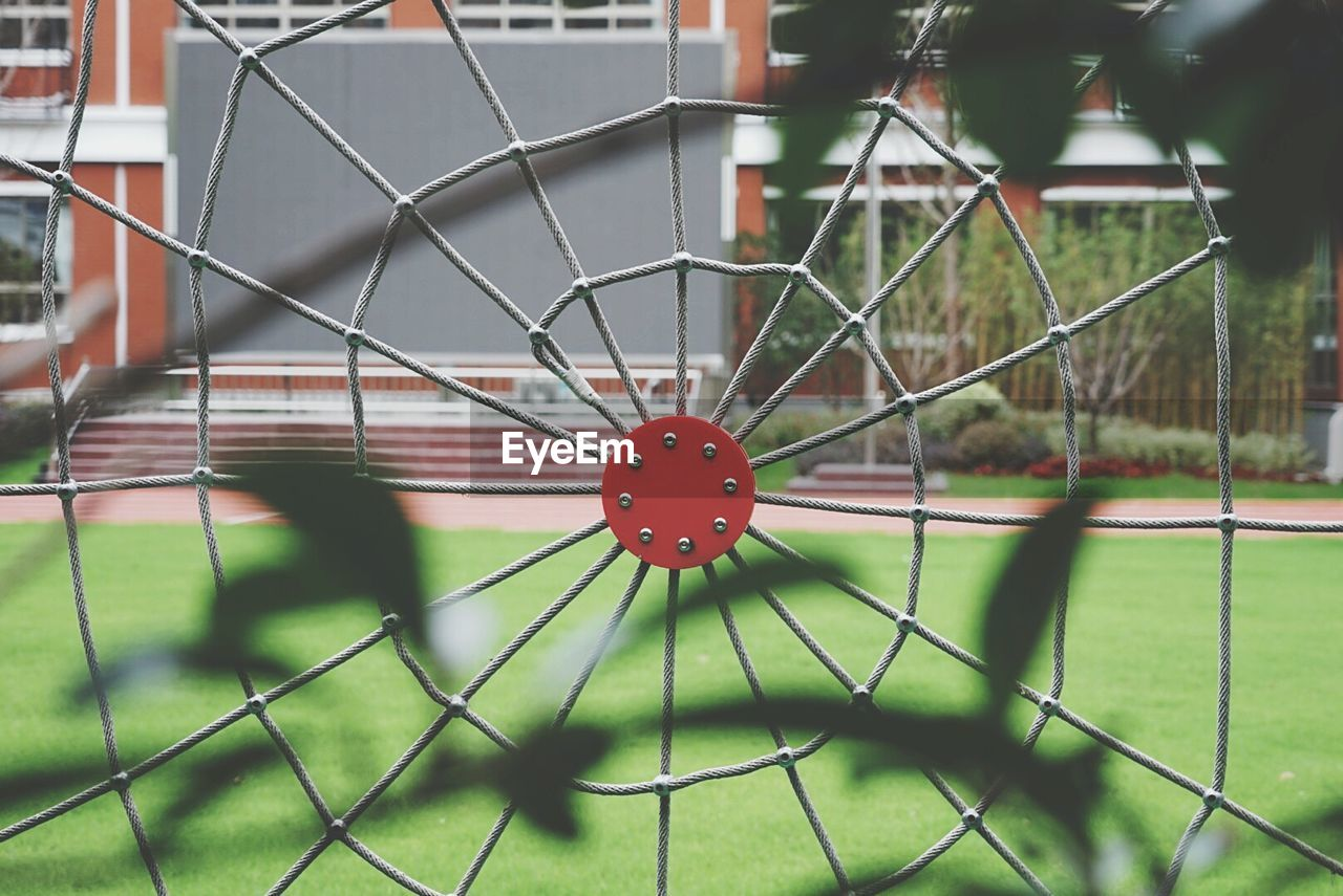 focus on foreground, no people, sport, close-up, day, fence, metal, green color, grass, pattern, outdoors, nature, barrier, plant, boundary, field, chainlink fence, built structure, security, selective focus, wheel
