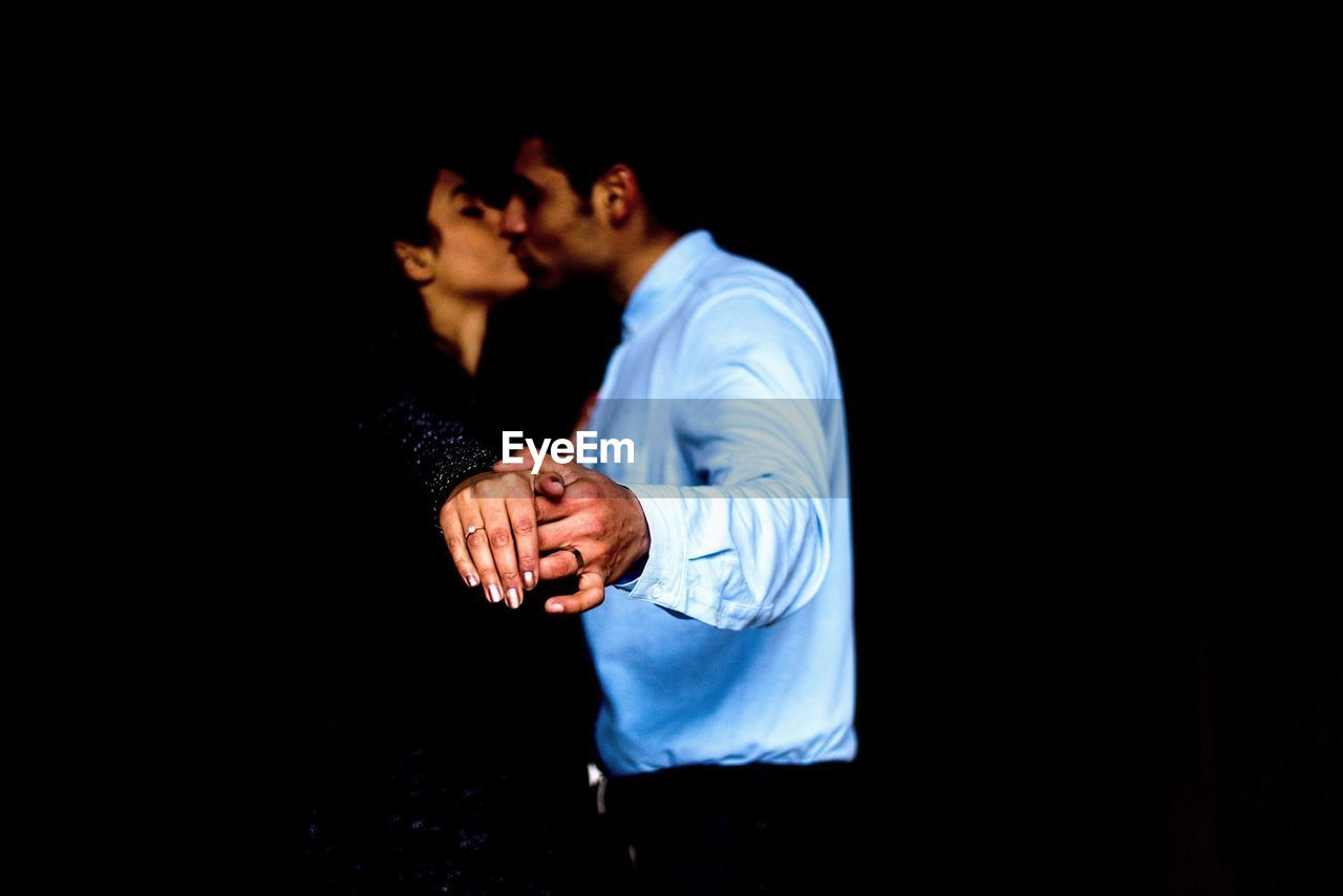 Side view of couple kissing while standing in darkroom