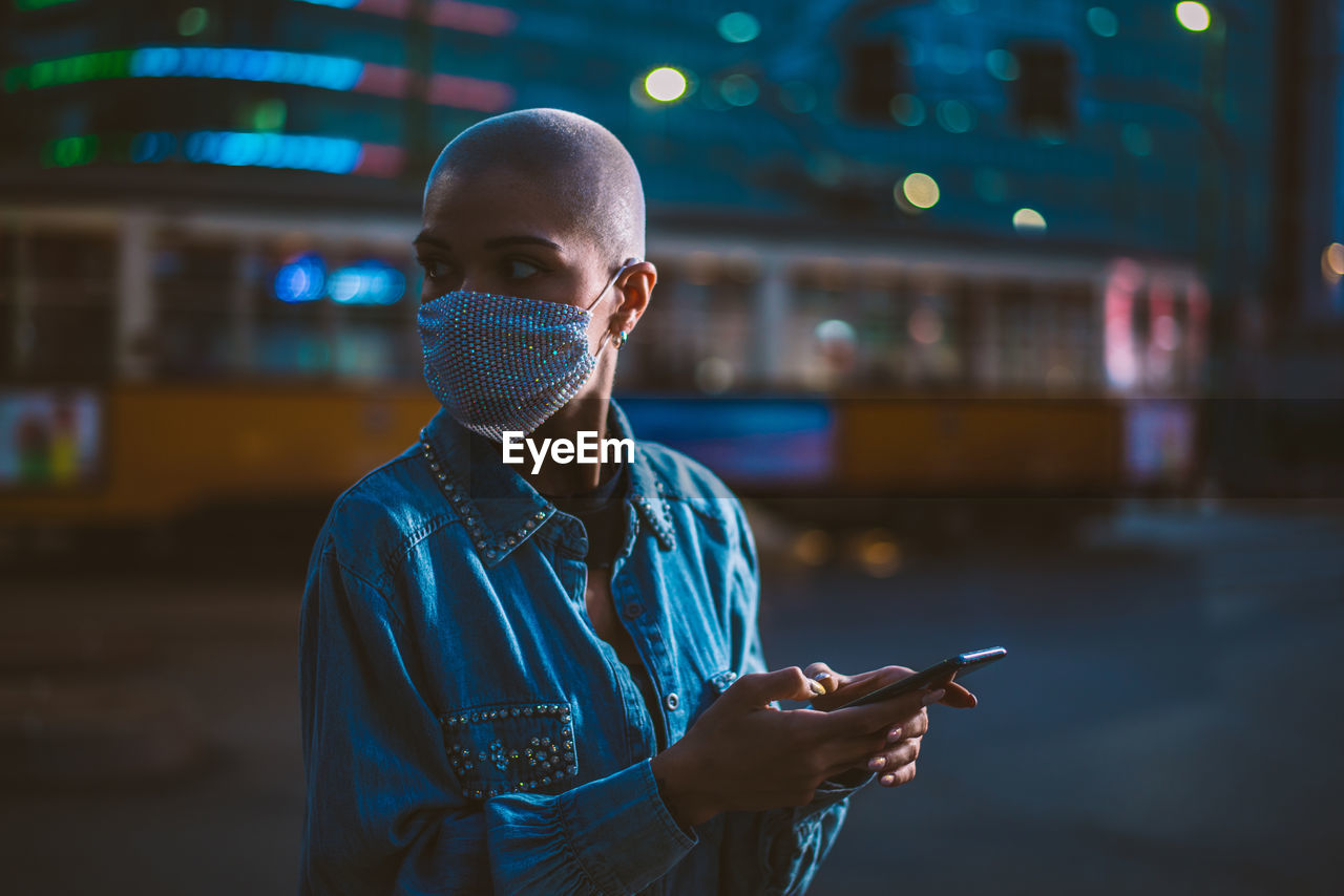 Young woman wearing mask with shaved head looking away while holding smart phone outdoors