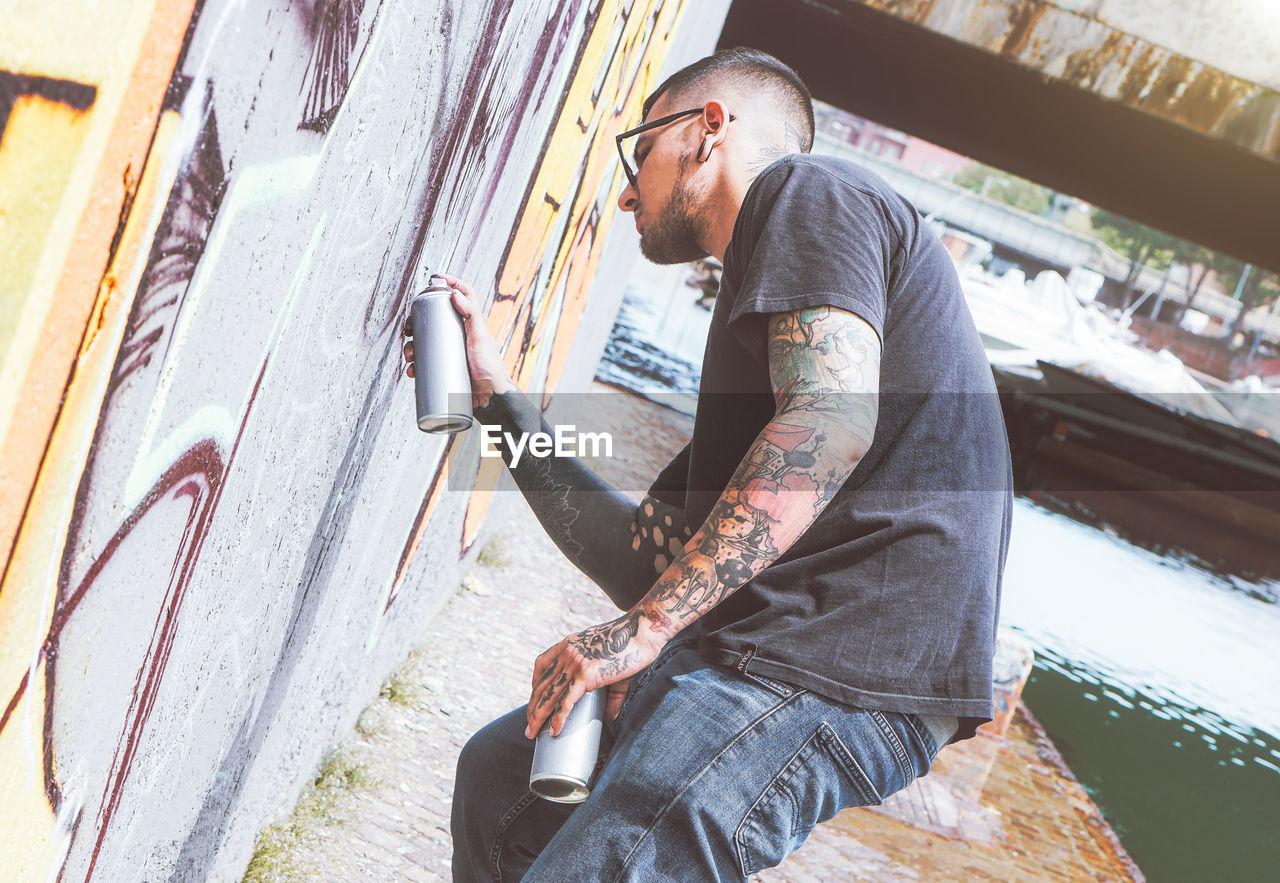 Man Spraying Paint On Wall
