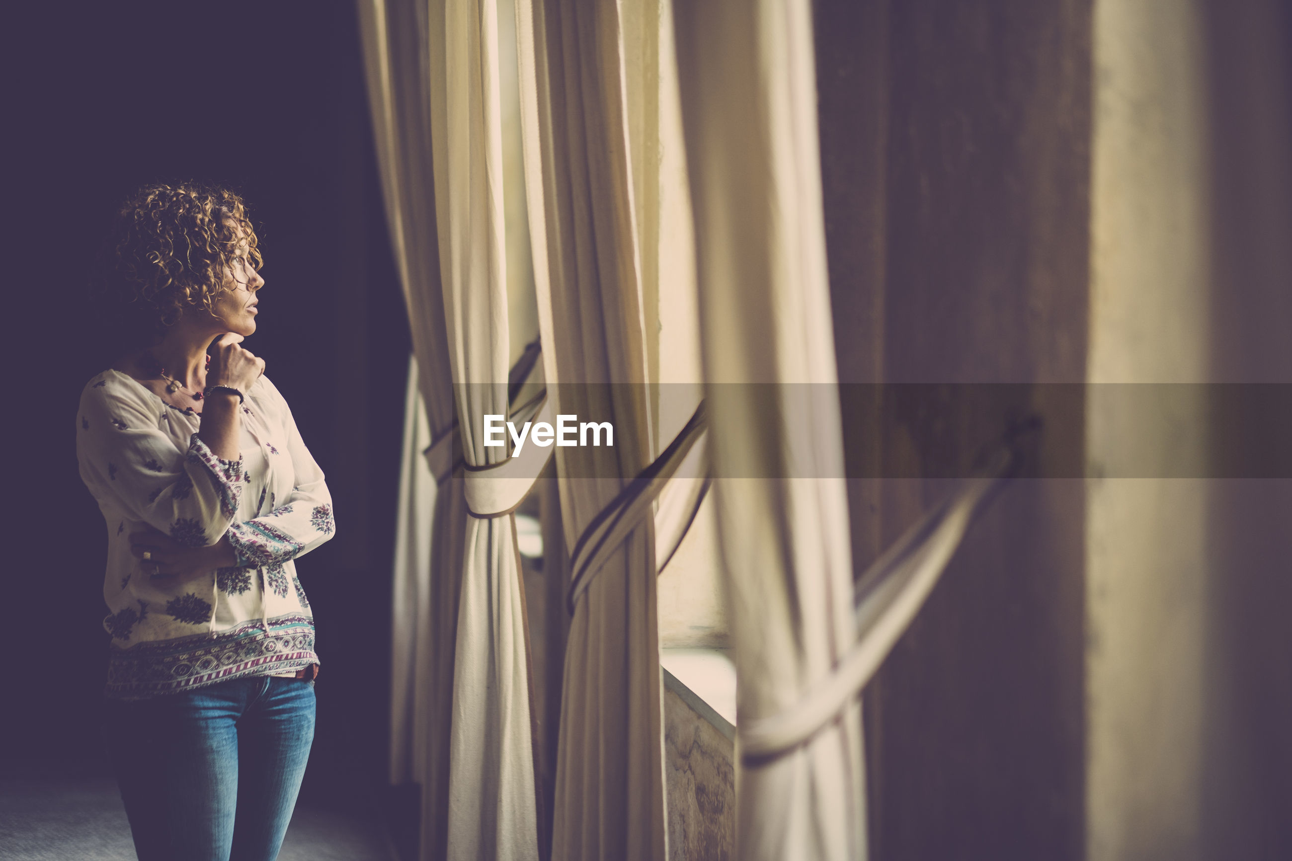 Woman looking through window while standing in corridor