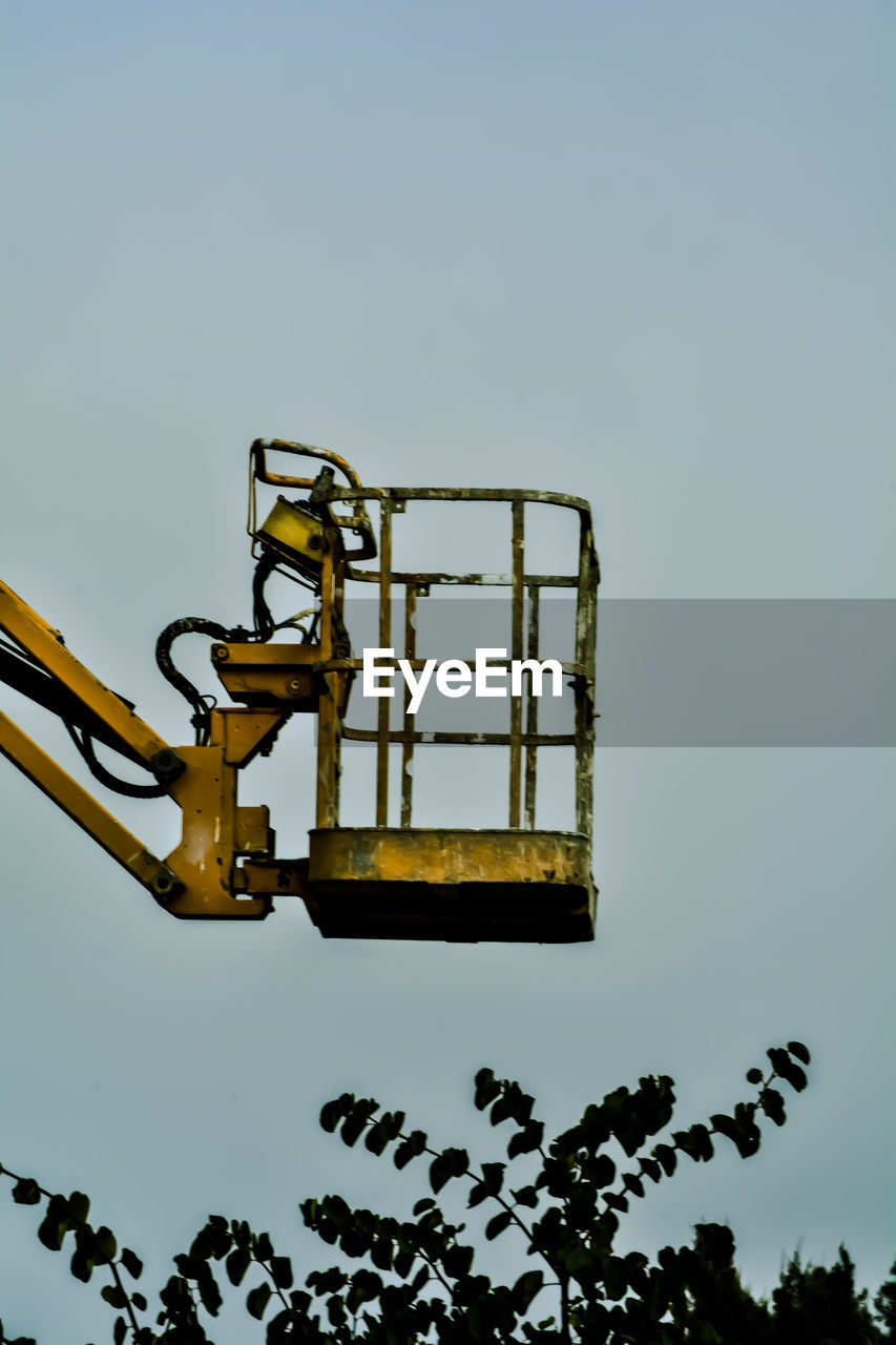 Low angle view of yellow cherry picker against sky