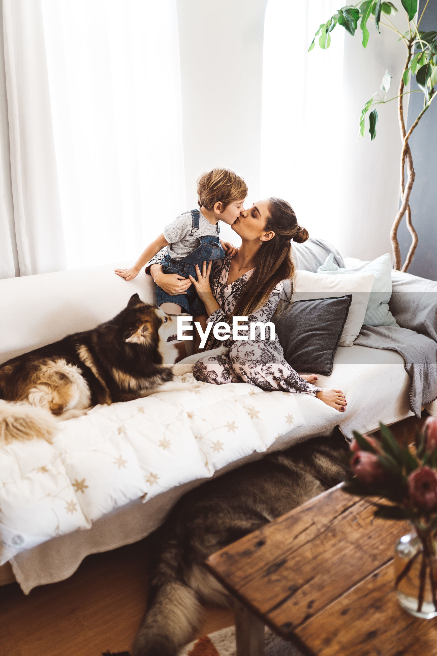 Boy and mother lying on sofa at home