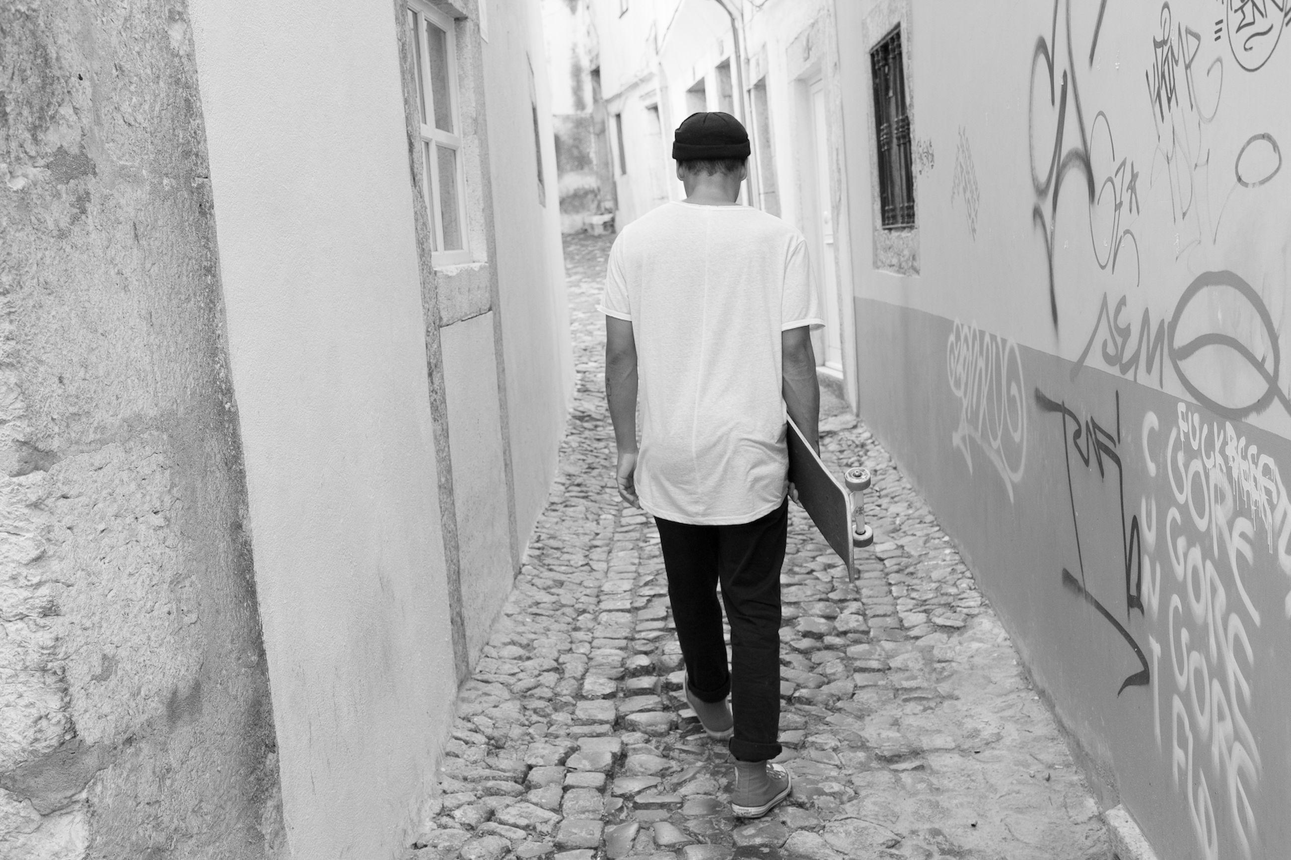 Rear view of man walking along buildings