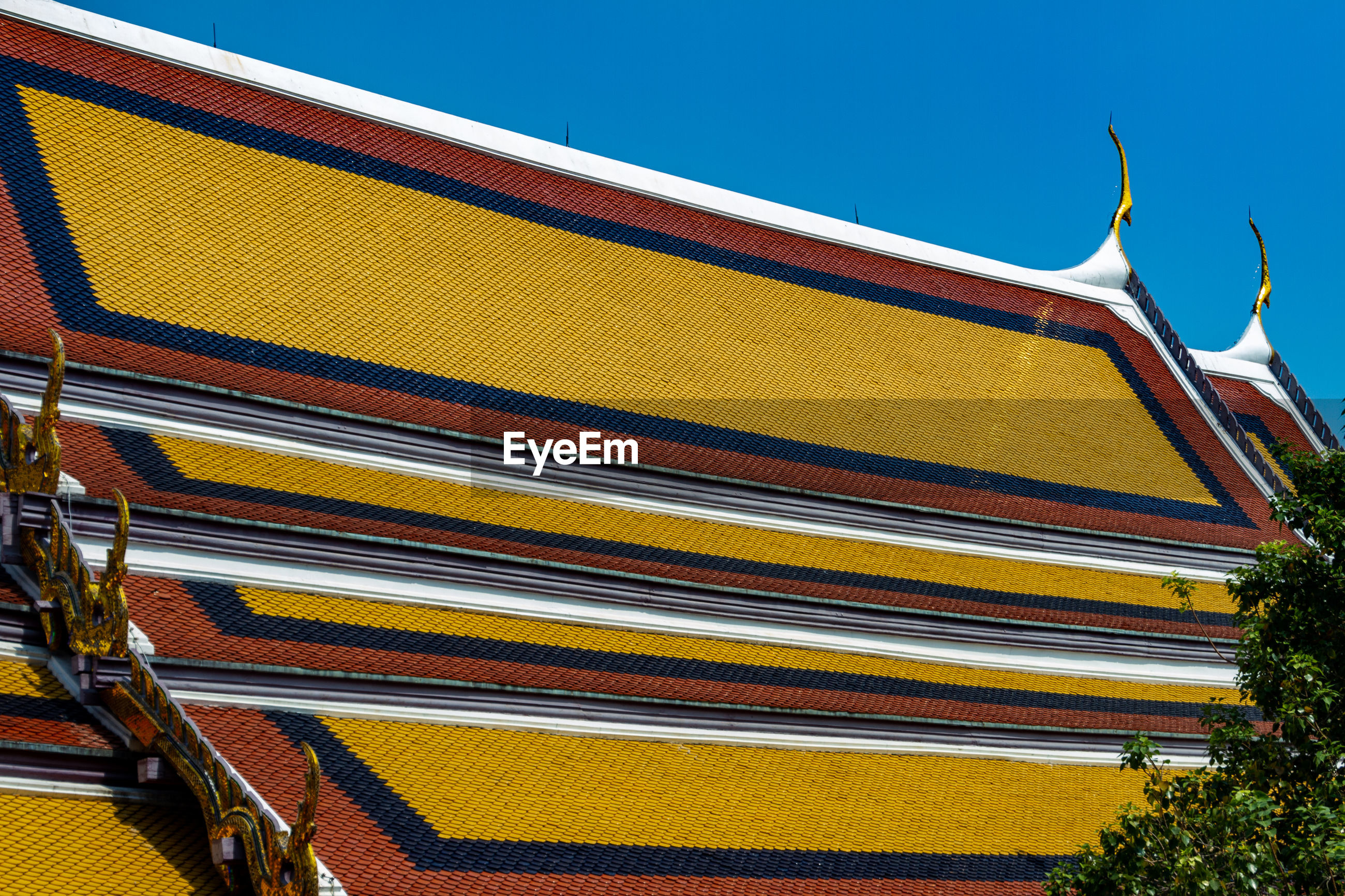 LOW ANGLE VIEW OF MULTI COLORED ROOF AGAINST SKY
