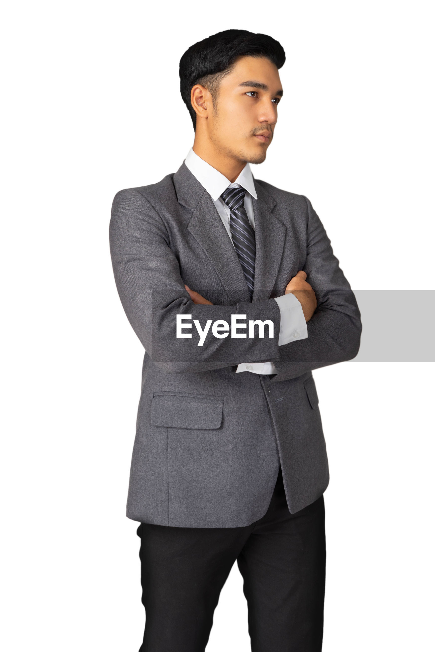 Young businessman standing against white background