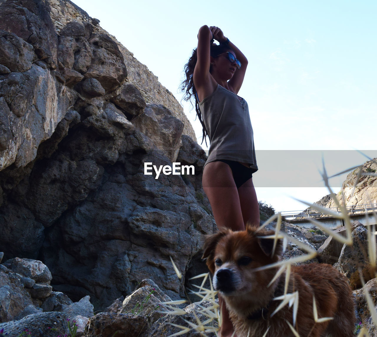 real people, mammal, leisure activity, domestic animals, rock - object, one animal, dog, one person, lifestyles, pets, nature, full length, clear sky, adventure, casual clothing, low angle view, standing, day, outdoors, young women, women, sky, young adult, beauty in nature