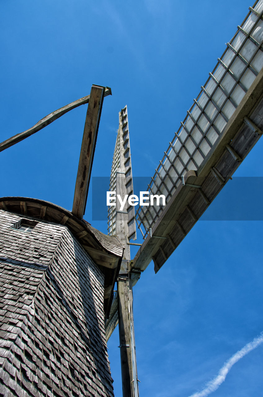 low angle view, sky, architecture, built structure, blue, day, nature, no people, fuel and power generation, alternative energy, building exterior, renewable energy, environmental conservation, cloud - sky, outdoors, sunlight, wind turbine, metal, wind power, turbine