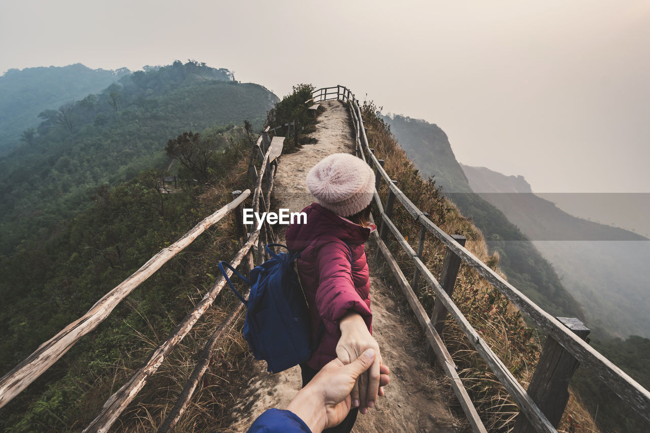 Woman holding person hand on mountains against sky during winter