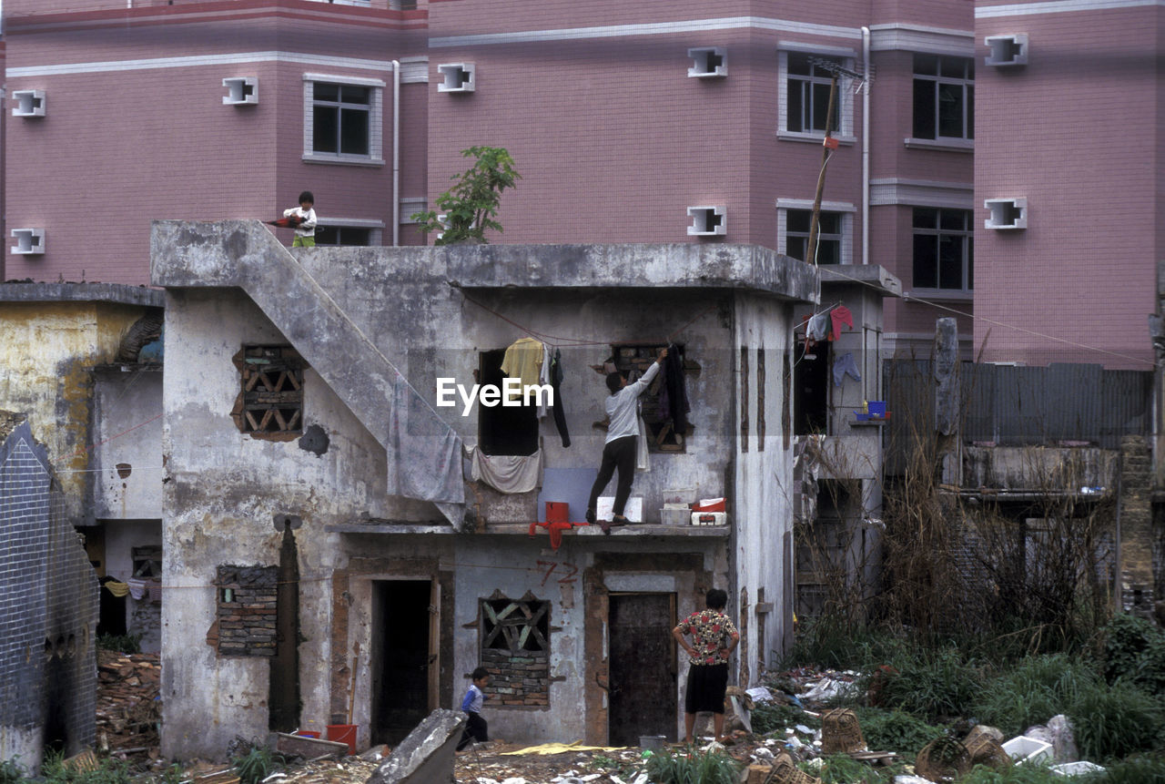 People At Damaged House Against Building