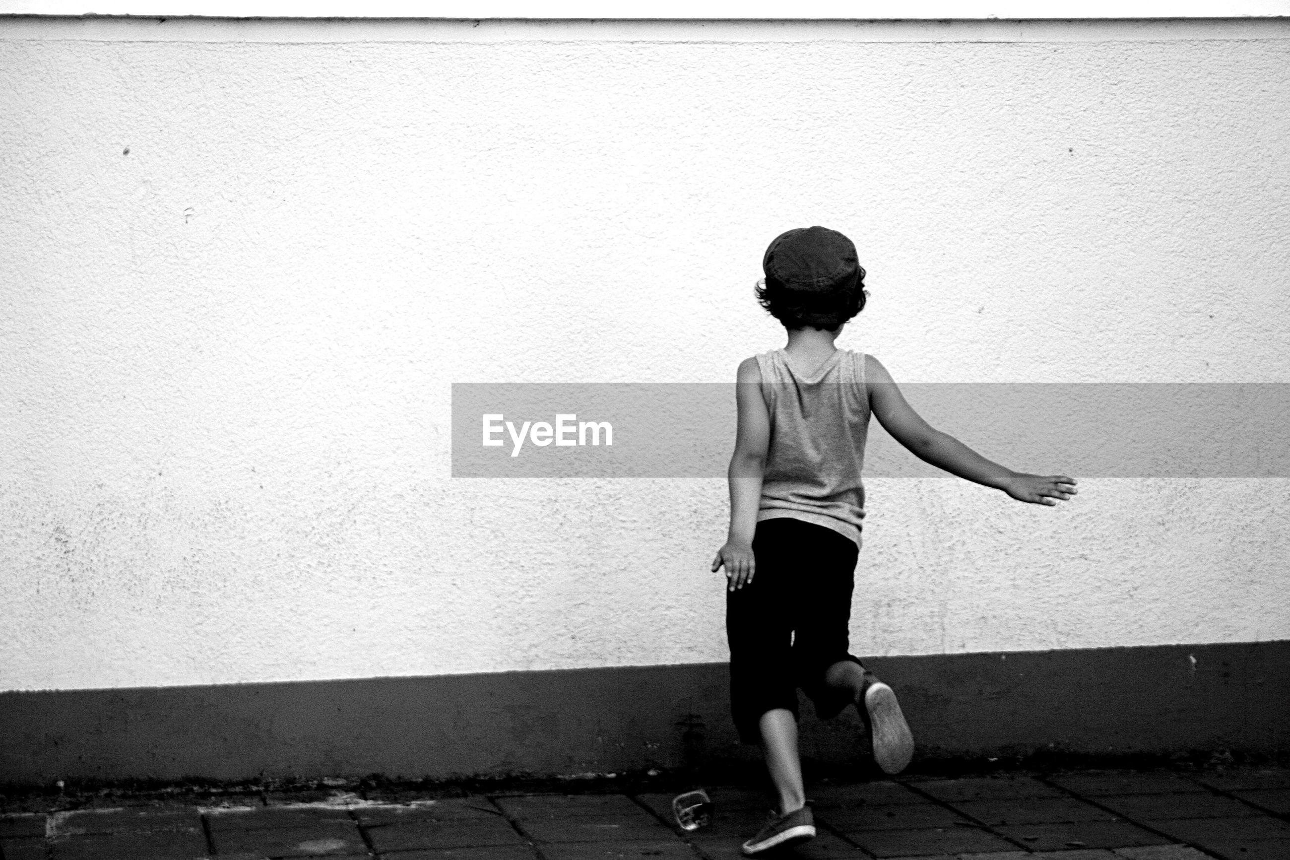 Boy running against wall