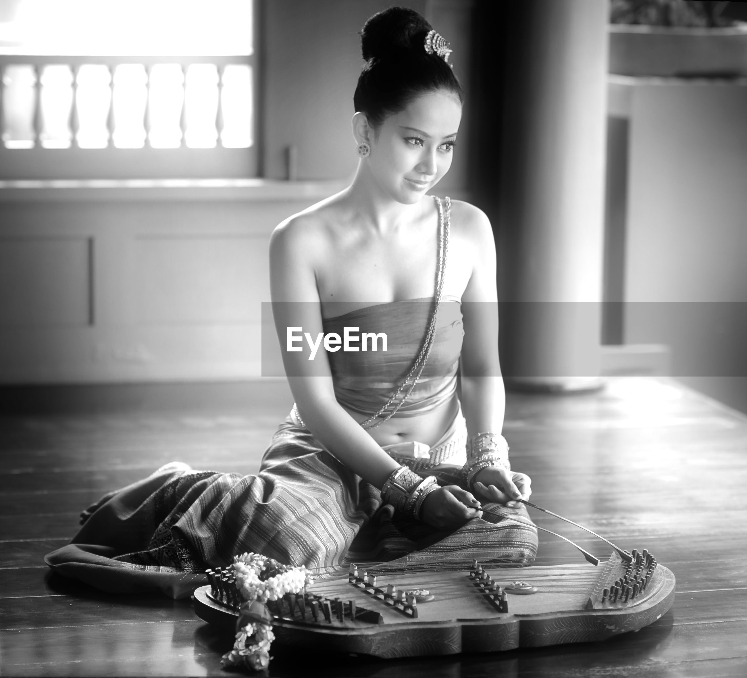 Beautiful woman wearing traditional clothing playing musical instrument on floor