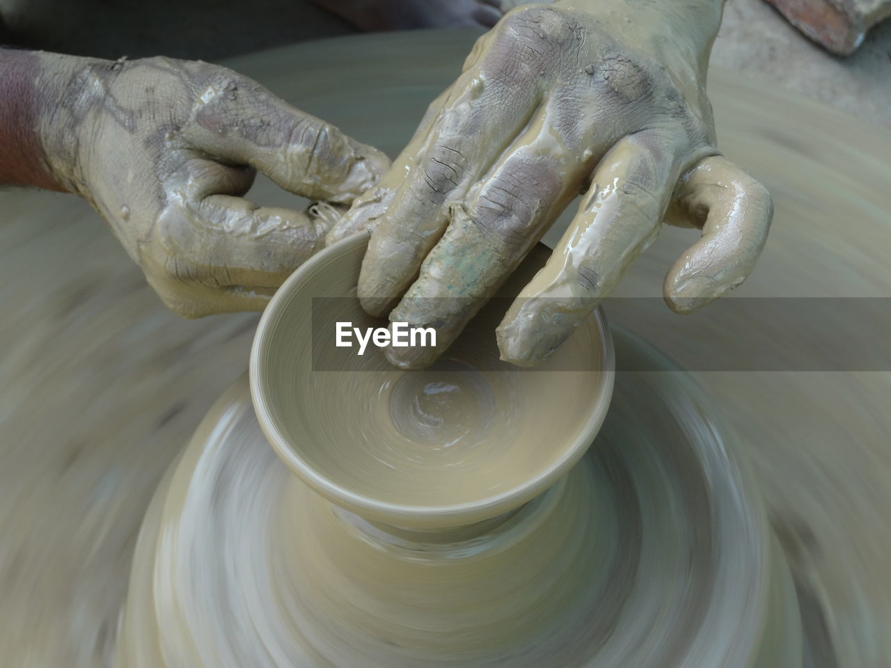 Cropped Hands Of Potter Making Clay Pot At Pottery
