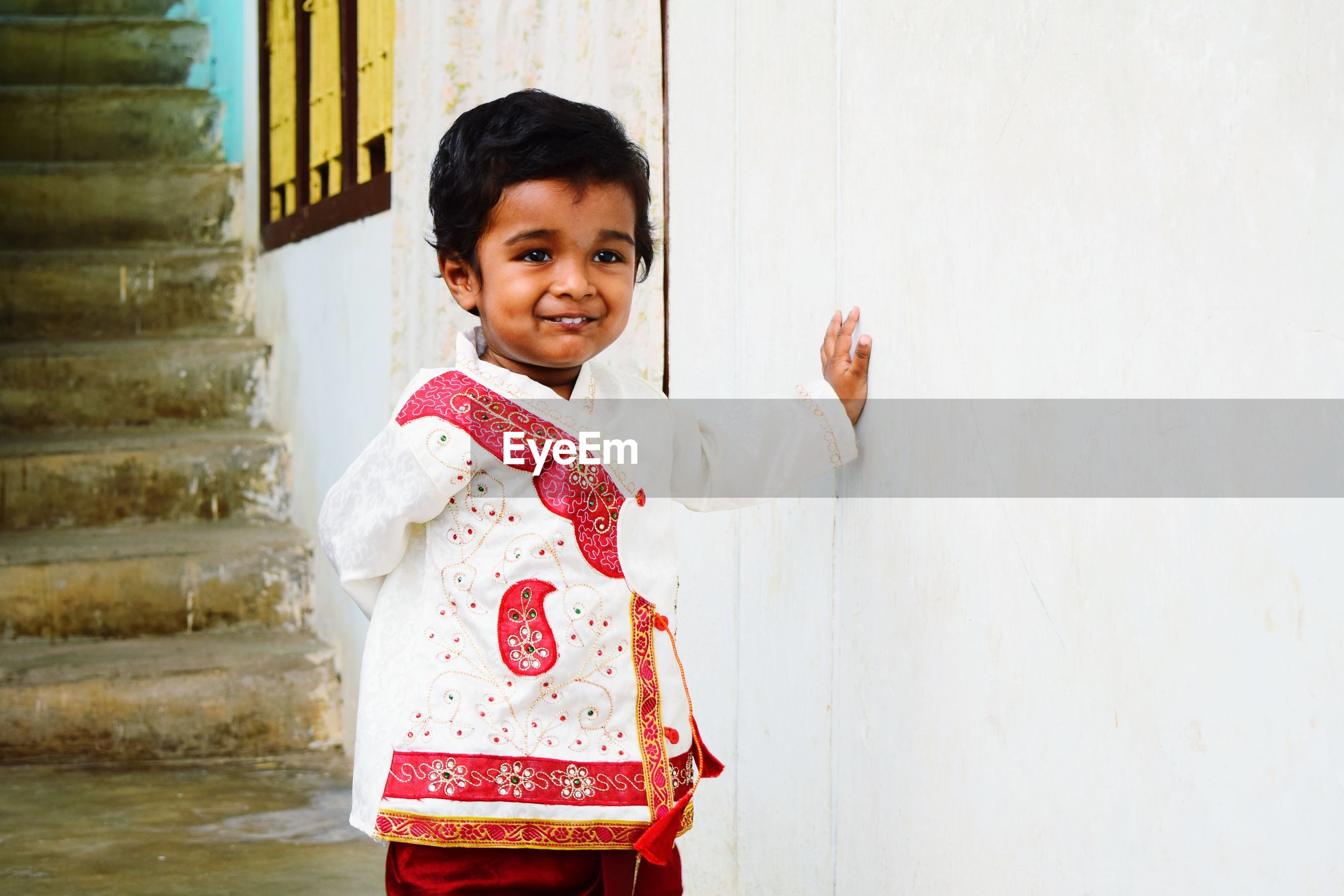 Smiling baby boy standing by wall