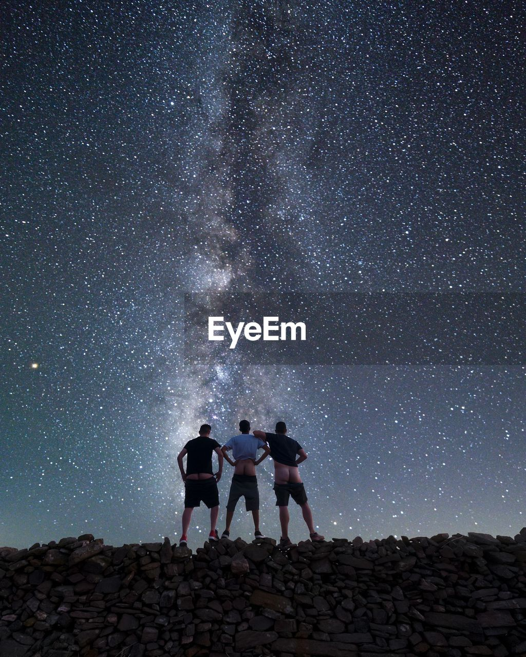 Rear view of friends showing buttocks while standing on stone wall against star field