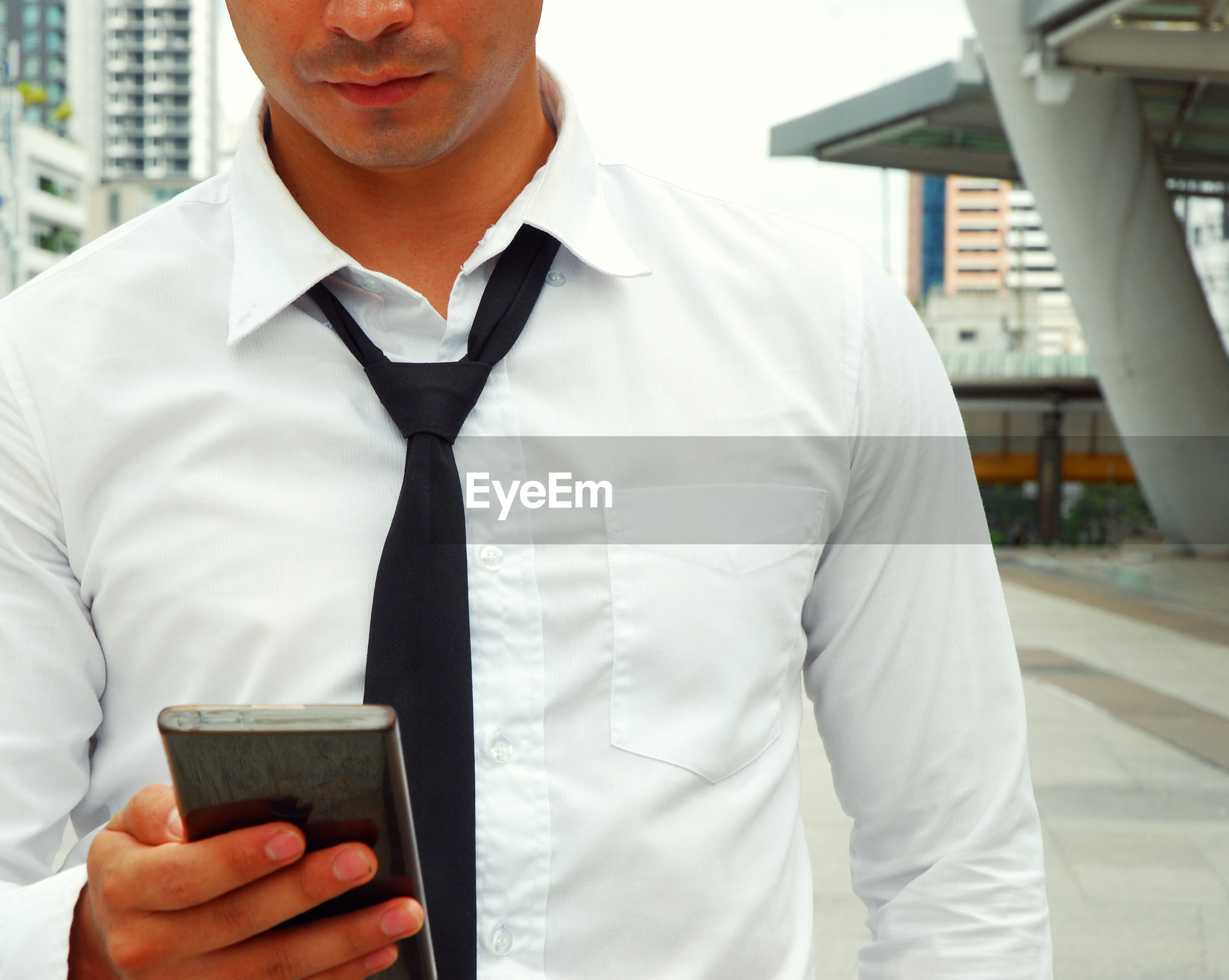 Midsection of man using mobile phone in city