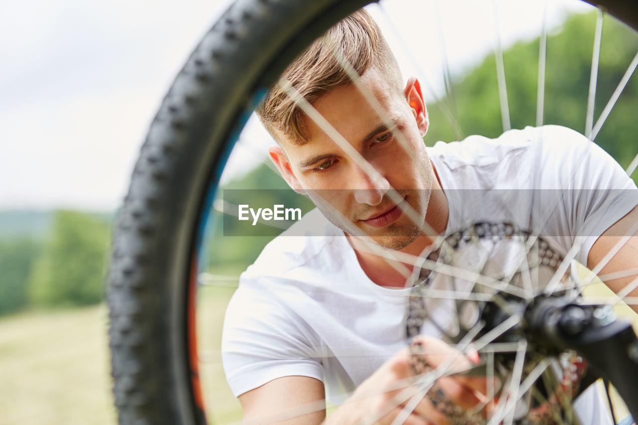Young Man Repairing Bicycle Against Sky In Park