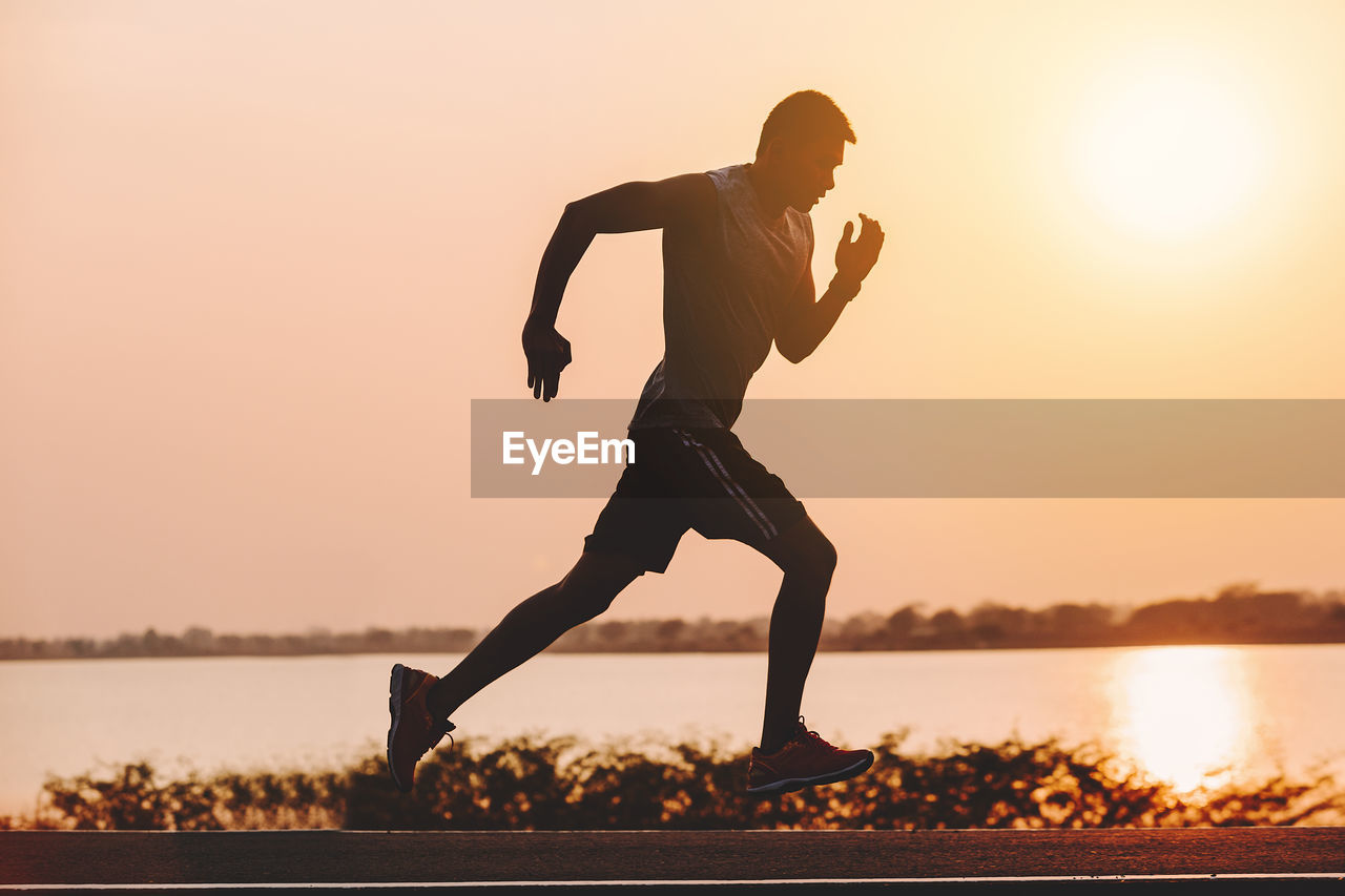 sunset, full length, sky, lifestyles, water, real people, one person, sport, leisure activity, men, nature, healthy lifestyle, orange color, exercising, clear sky, lake, sunlight, outdoors, effort, physical activity, teenager