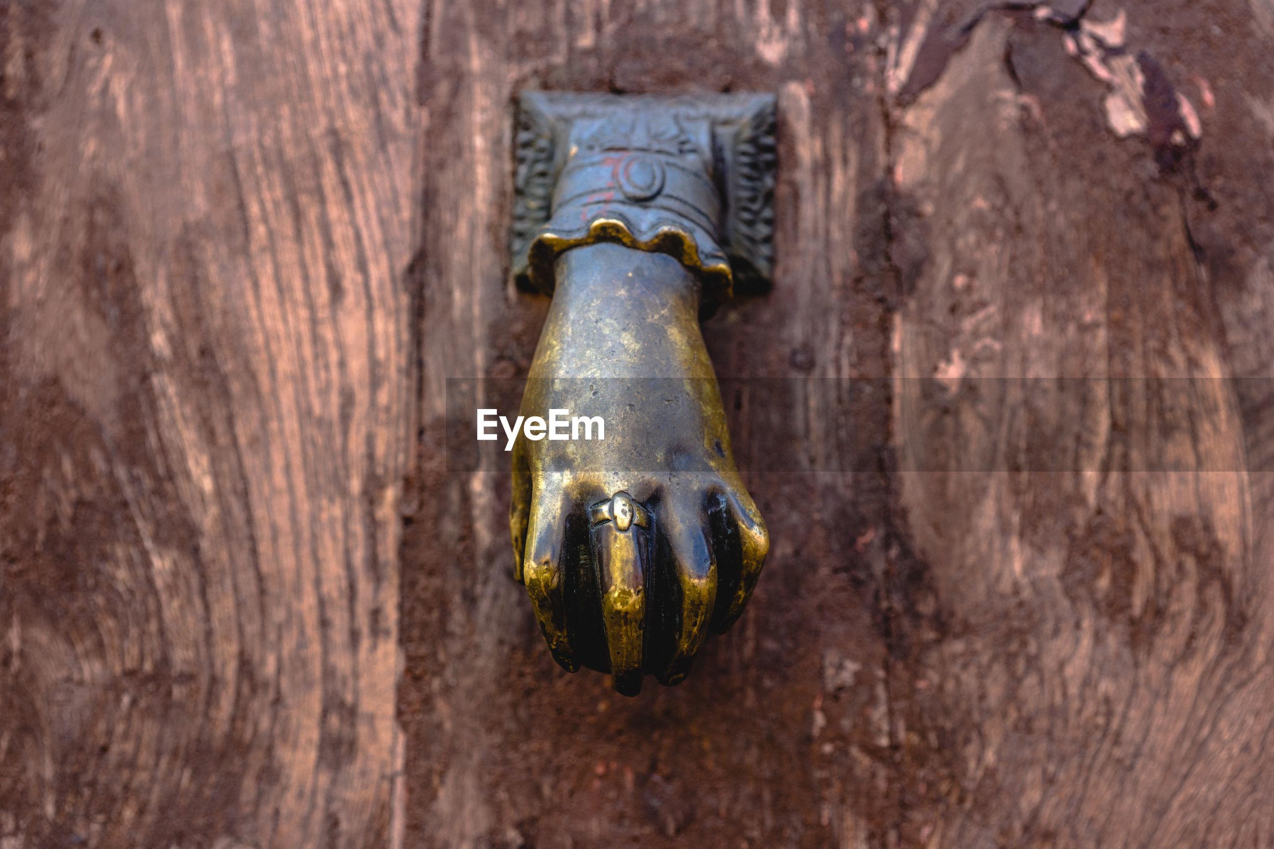 CLOSE-UP OF DOOR KNOCKER ON METAL