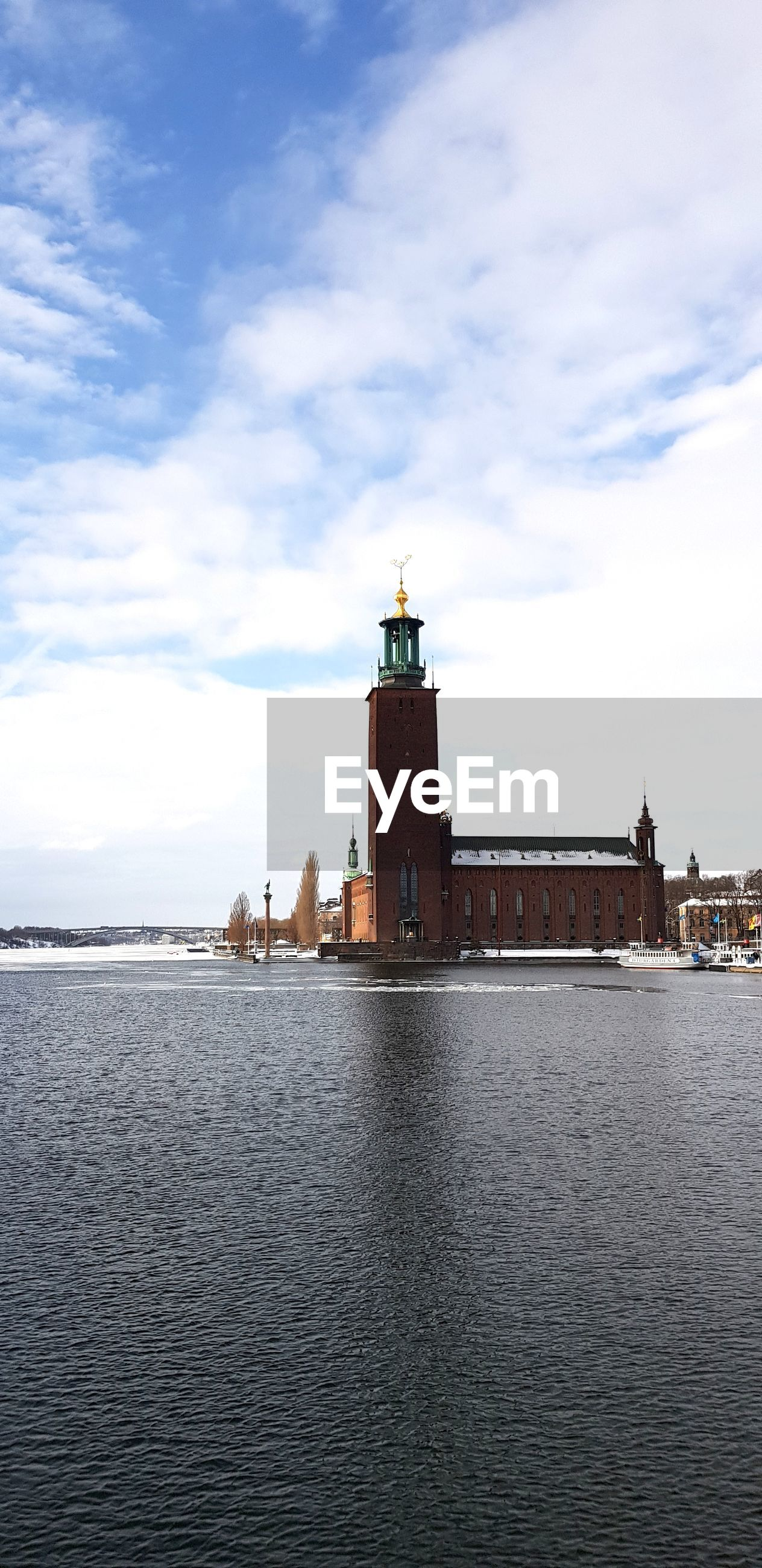 Stockholm city hall by river canal against sky