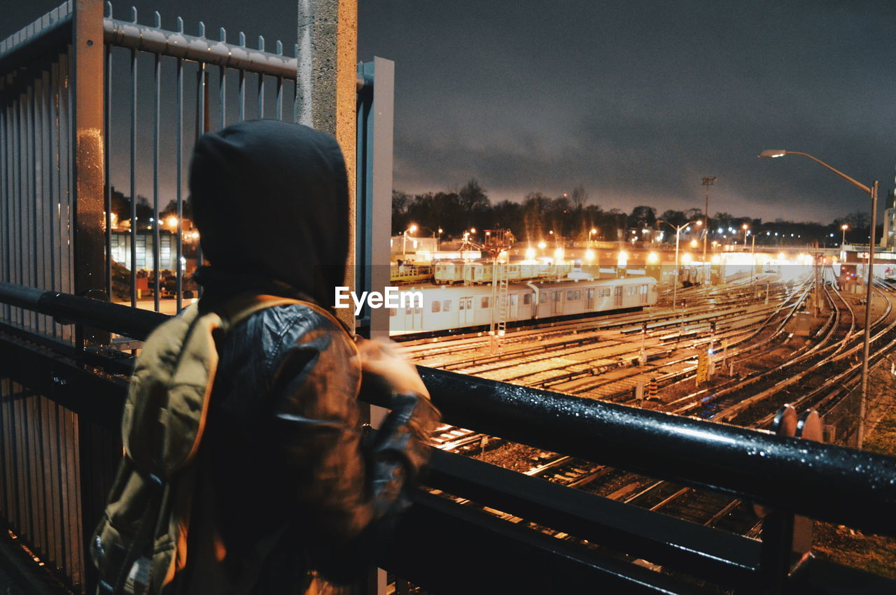 Rear View Of Person Standing By Railing Over Illuminated Railroad Track Against Sky At Night