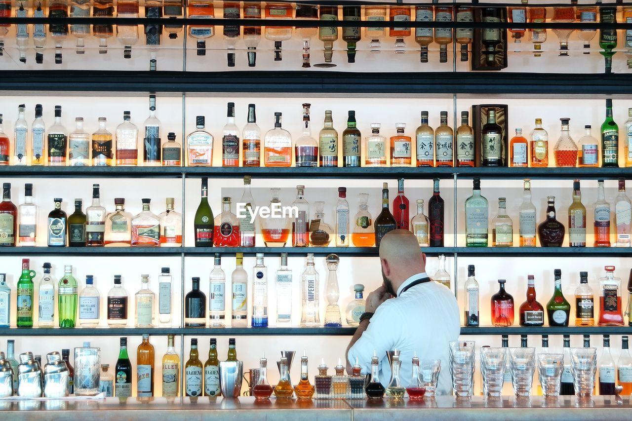 Bartender against arranged bottles in shelf