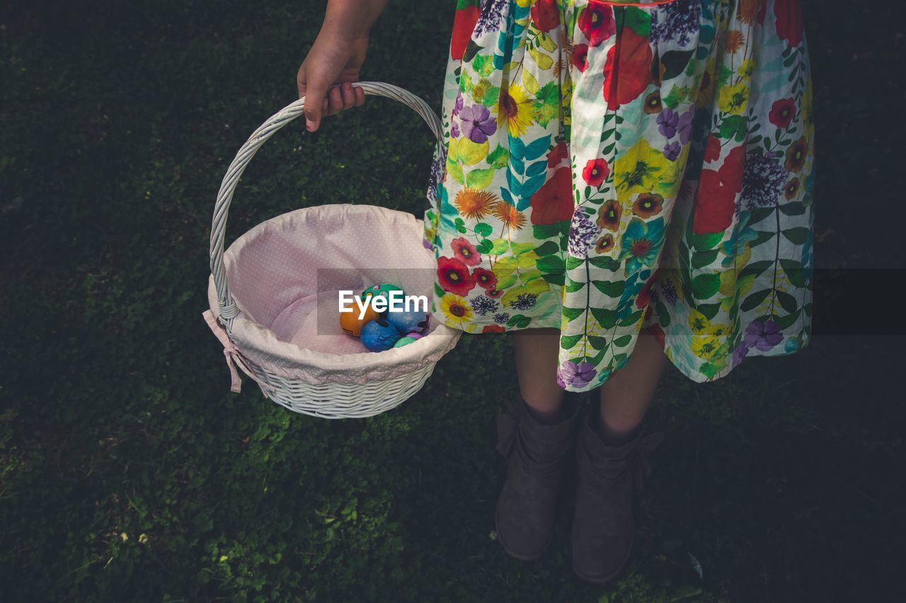 Low Section Of Girl Holding Easter Eggs In Wicker Basket While Standing On Grassy Field