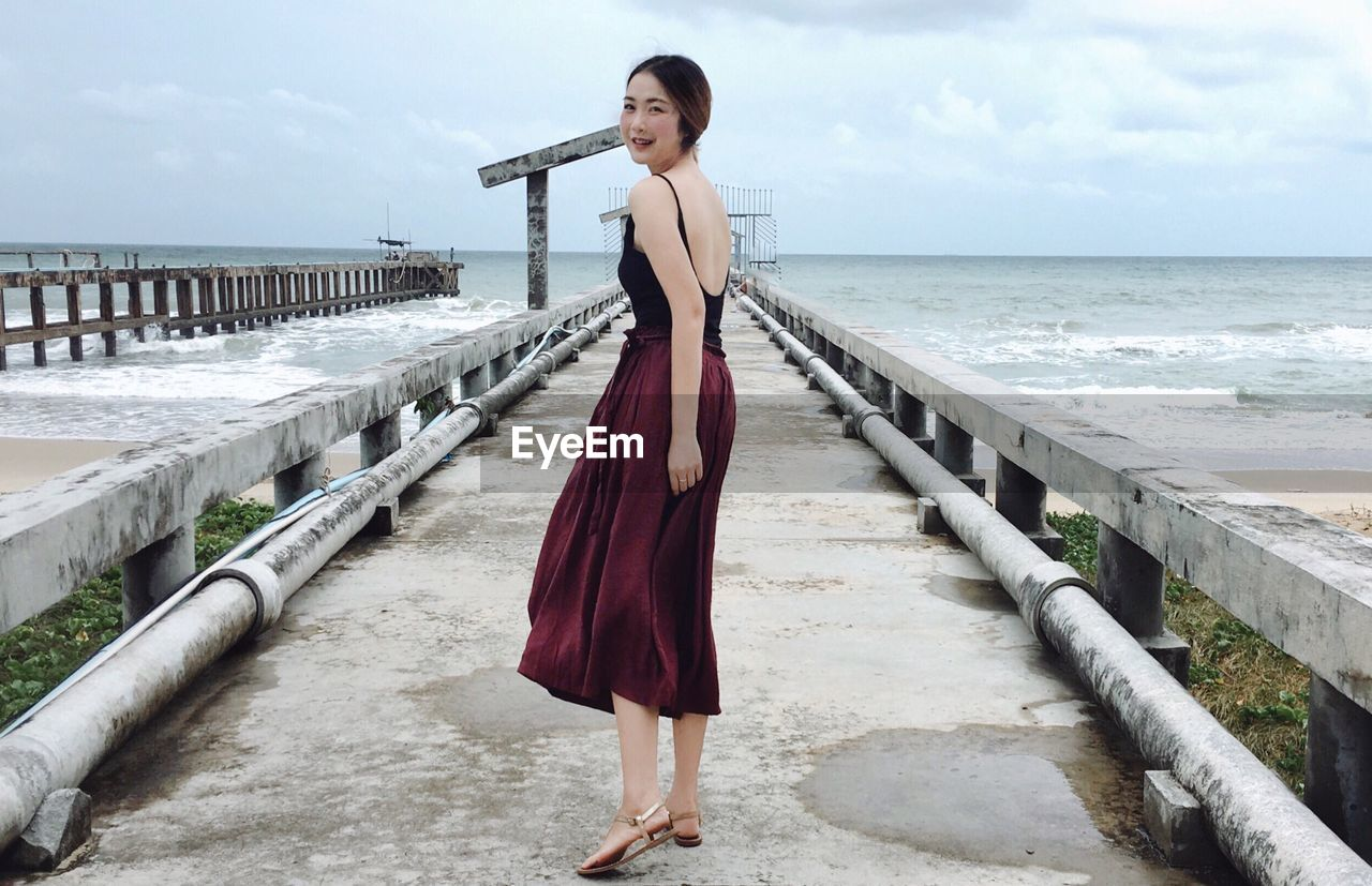 Portrait of beautiful young woman standing on bridge against sea