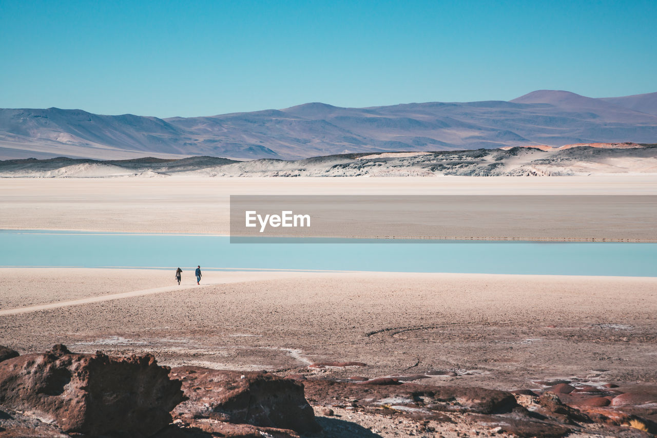 beauty in nature, nature, scenics, tranquil scene, mountain, tranquility, outdoors, lake, water, day, real people, arid climate, landscape, one person, mountain range, physical geography, salt flat, blue, desert, salt - mineral, sky, men, clear sky, salt basin, people