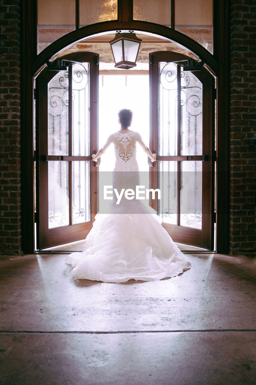 full length, one person, indoors, real people, women, lifestyles, adult, rear view, window, day, architecture, leisure activity, wedding, wedding dress, bride, clothing, event, young women, young adult, contemplation