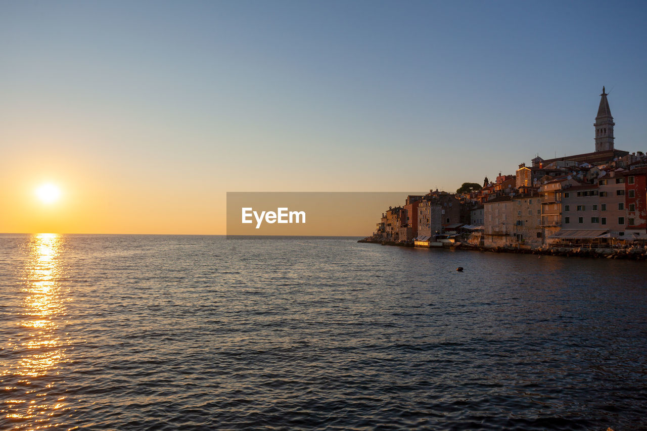 SCENIC VIEW OF SEA AGAINST BUILDINGS AGAINST SKY DURING SUNSET
