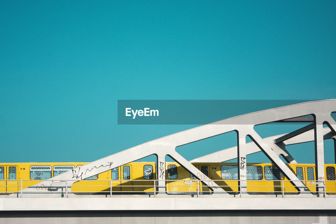 Low angle view of train on bridge against clear blue sky