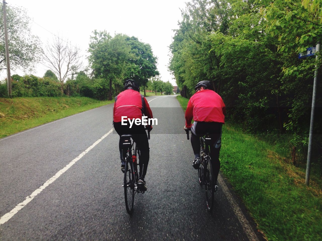 Rear View Of Two People Bicycling On Road