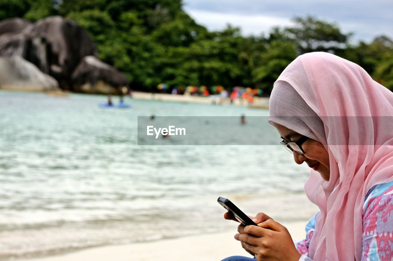 Midsection Of Woman Holding Smartphone On Beach
