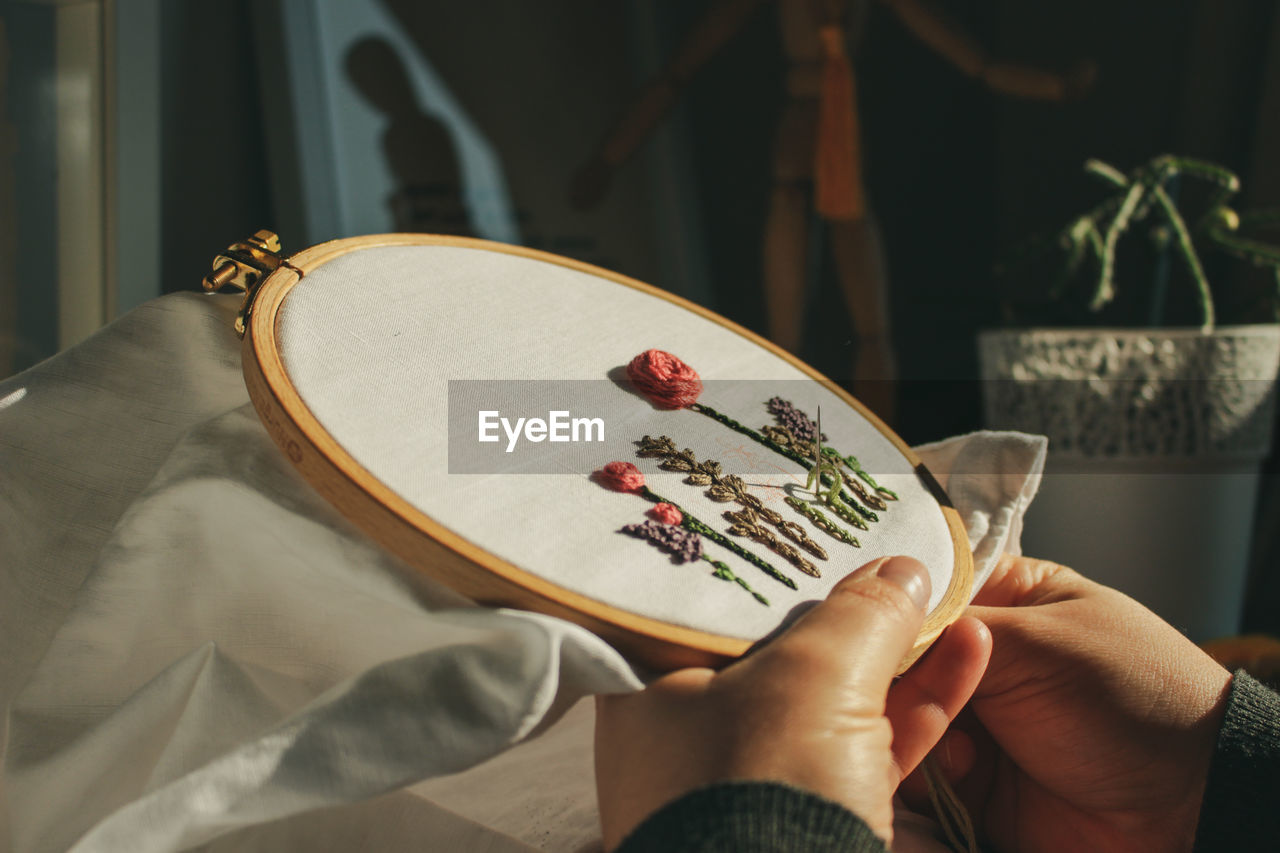 Midsection of person hand embroidering