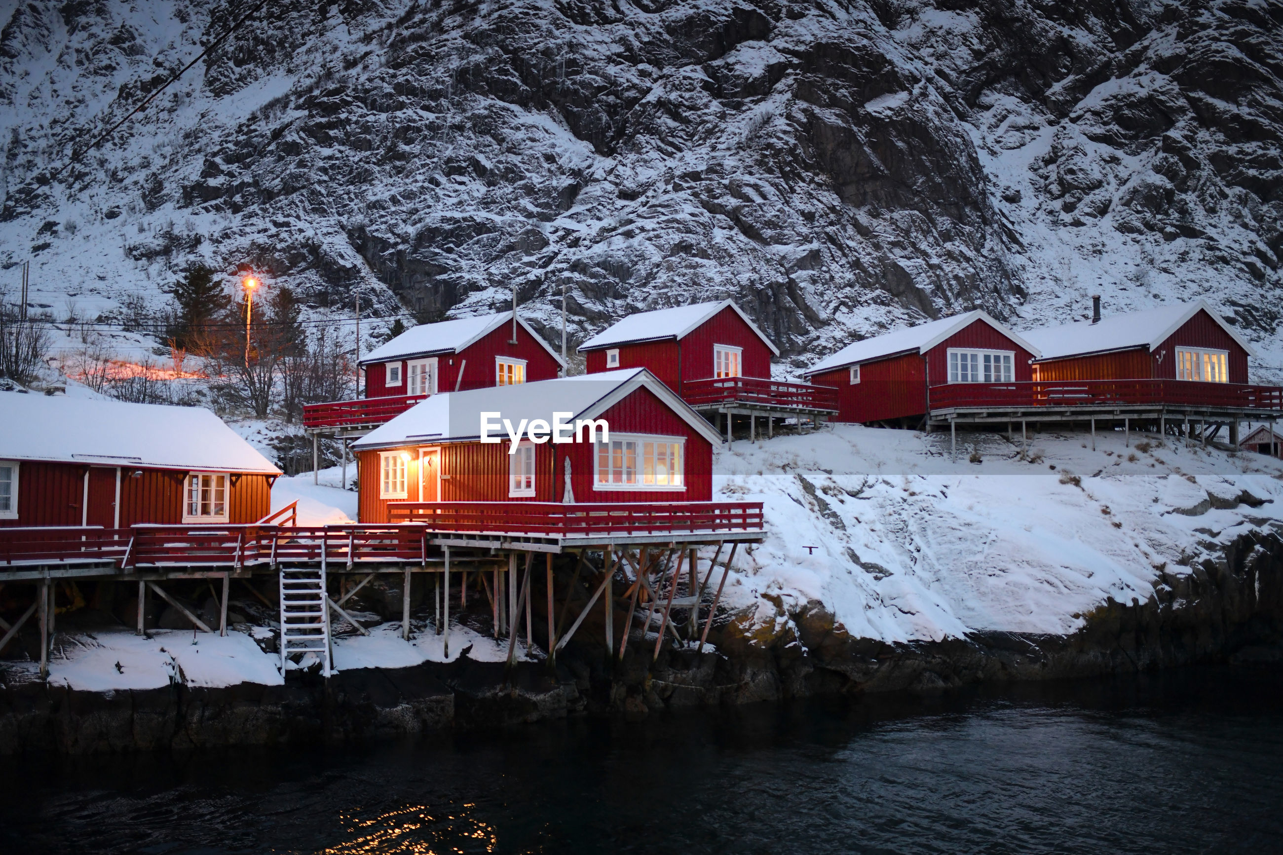 HOUSES BY FROZEN LAKE BY HOUSE DURING WINTER