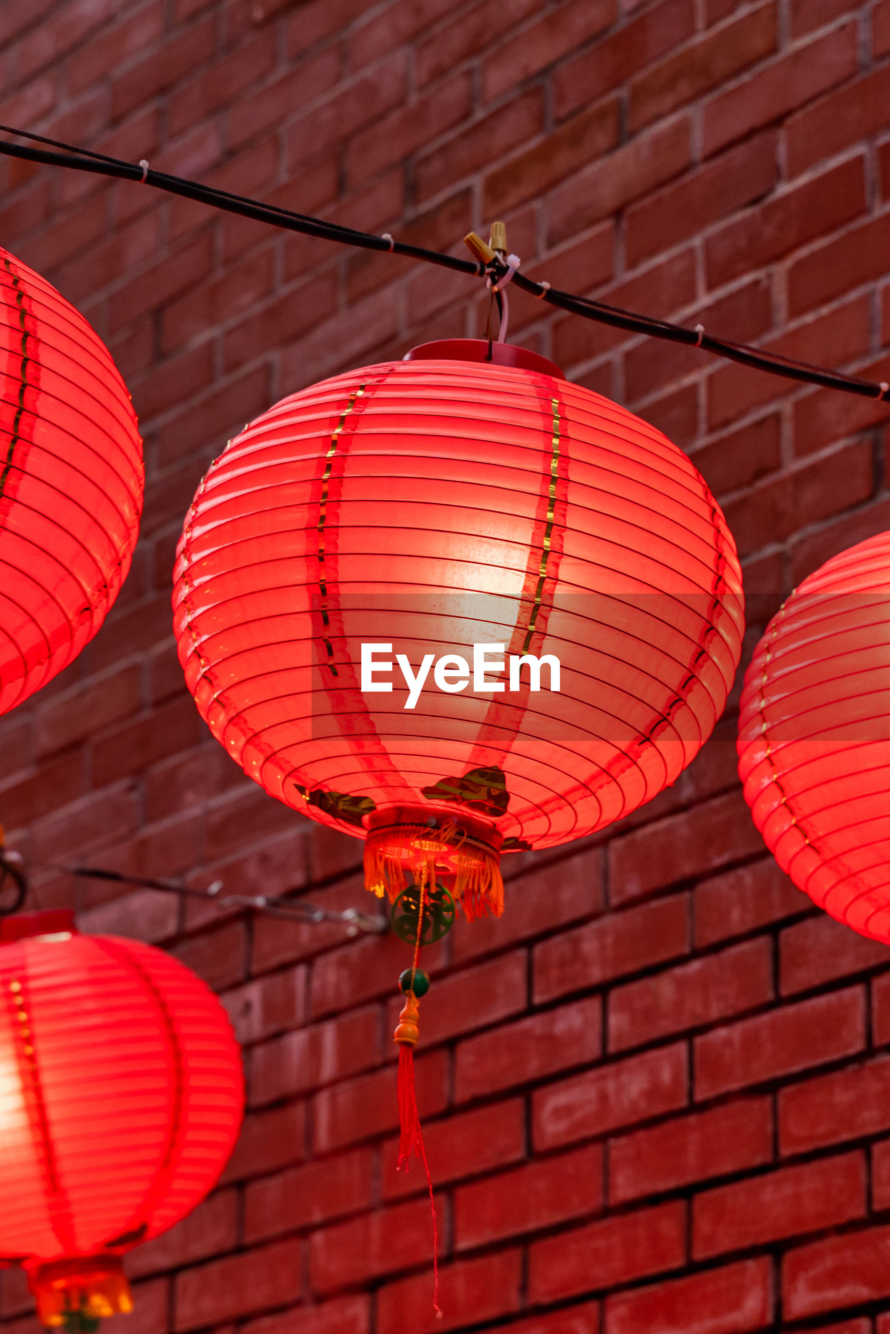 LOW ANGLE VIEW OF ILLUMINATED LANTERN HANGING AGAINST WALL