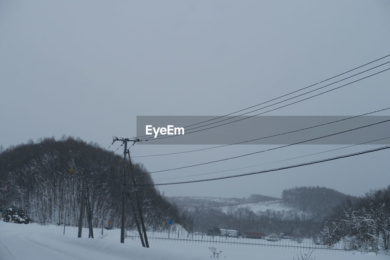 winter, snow, cold temperature, tree, cable, sky, electricity, plant, nature, no people, scenics - nature, beauty in nature, landscape, environment, power line, connection, technology, field, land, outdoors, power supply, snowcapped mountain, snowing